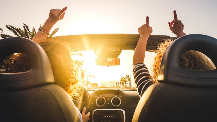 Couple of woman friends traveling and driving having a lot of fun dancing in the car with opened roof and summer vacation sunset ocean in front - concept of friendship together and nice lifestyle for independent girls.