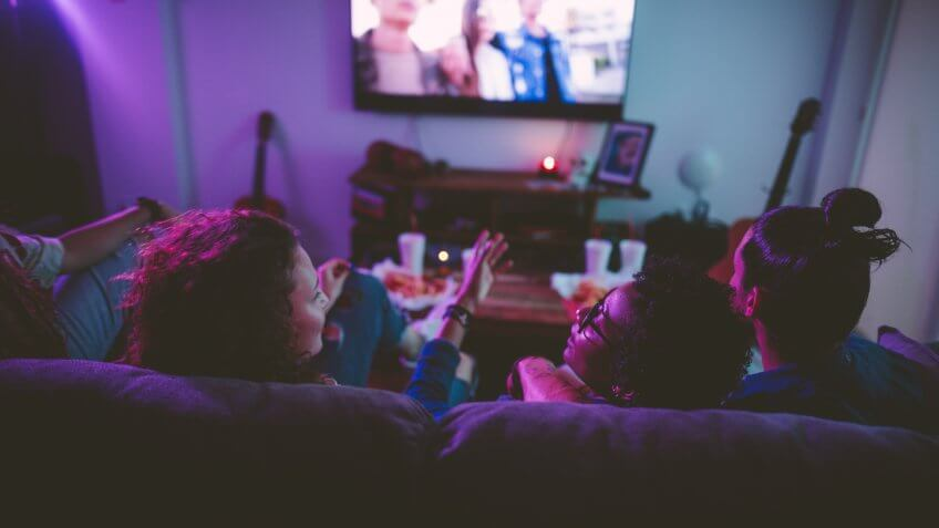 Young multi-ethnic hipster friends relaxing on living room sofa and watching film on TV.