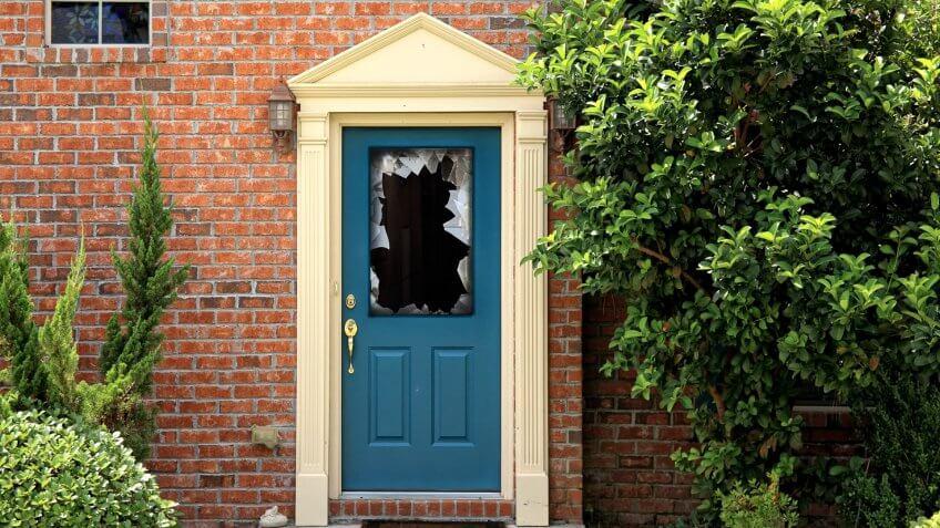 close up shot of broken door window glass of brick house.