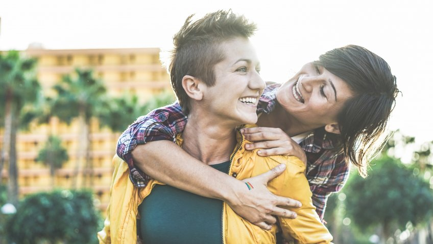 Happy gay couple having fun together outdoor - Young women having a date - Equality right, homosexuality lifestyle, lgbt, and relationship concept - Focus on left girl - Soft contrast filter.