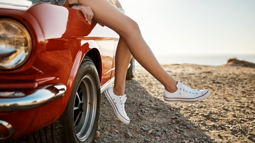 Cropped shot of a young woman relaxing on the hood of her car on a road trip.