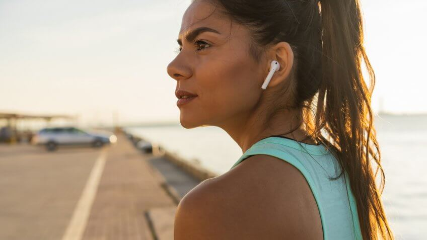 Tired fitness woman sweating taking a break listening to music on phone after difficult training.