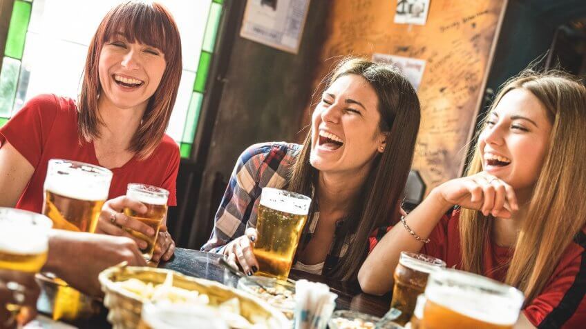 Happy girlfriends women group drinking beer at brewery bar restaurant - Friendship concept with young female friends enjoying time and having genuine fun at cool vintage pub - Focus on left girl.