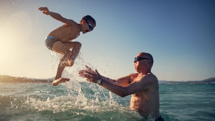 Little boy playing with his grandfather in the sea.