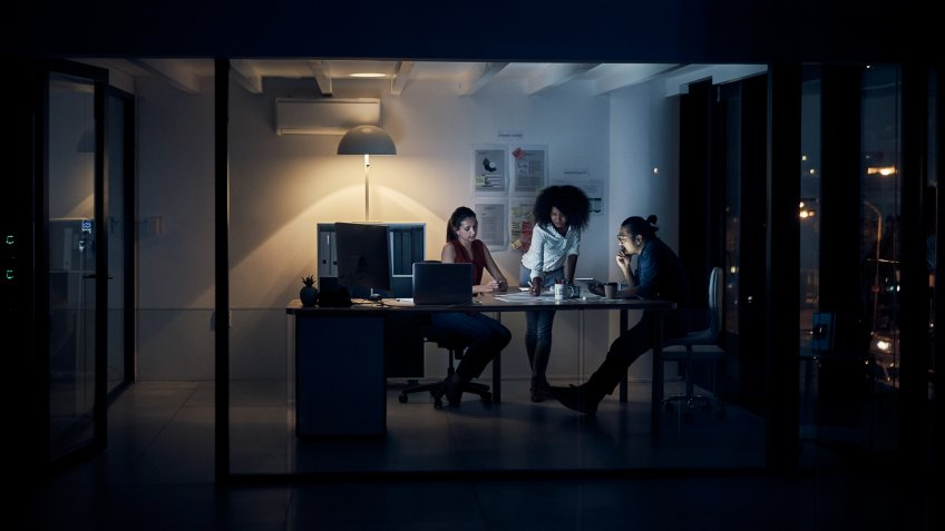 Full length shot of three young creative businesspeople meeting in their office at night.