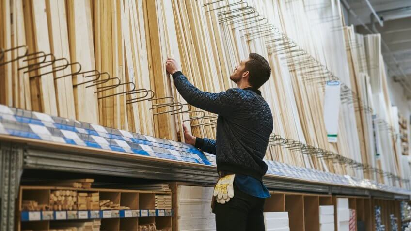 guy choosing wood in hardware store