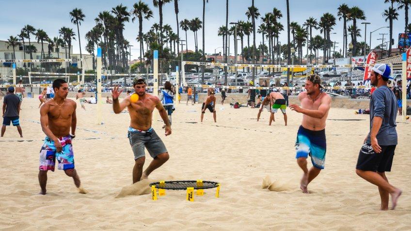 guys playing spikeball on the beach