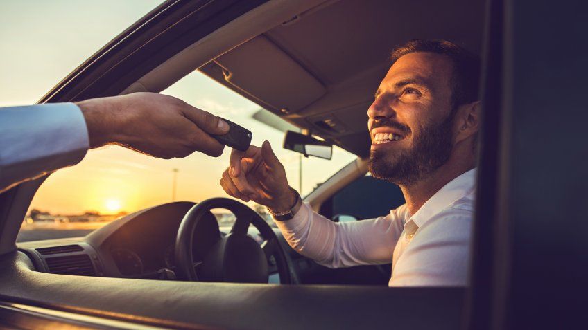 Happy businessman taking the car keys from unrecognizable person at sunset.
