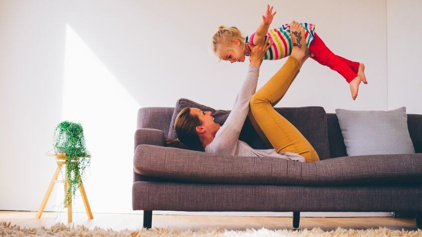 Mother balancing her little girl on her feet as she lays on the sofa on her back.
