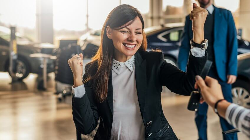 Cheerful young woman receiving the keys of her new car at car dealership.