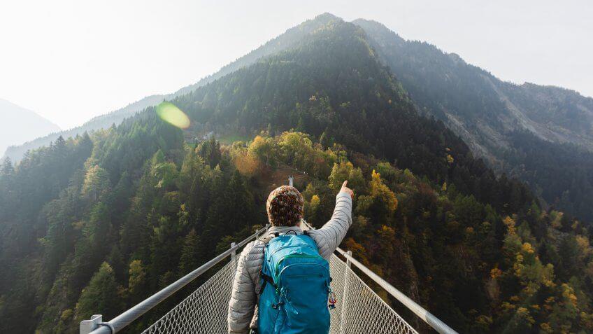 Solo hiker on suspension bridge between two mountain valleys.