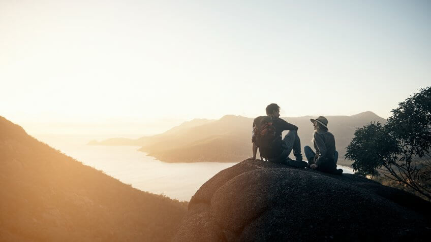 Shot of a young couple hiking the mountains in the morning.