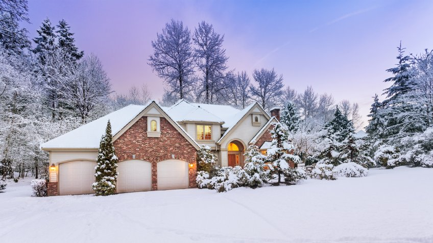 Daylight fades over a snow-covered suburban home - Image.