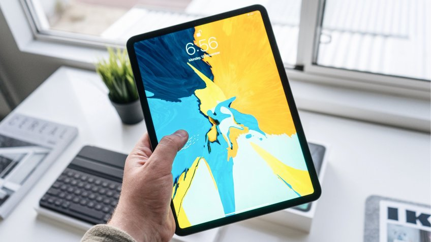 holding a recent model iPad device