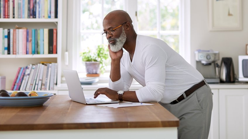 Shot of a mature man using a laptop while working out his finances at home.