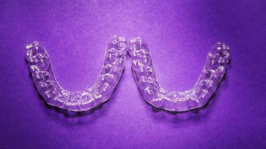 Isolated transparent teeth prosthesis over purple for design.