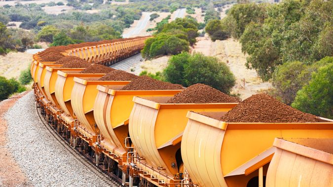 Heavy train loaded with brown hematite iron ore in orange freight wagons (cars) passes through rolling hills.
