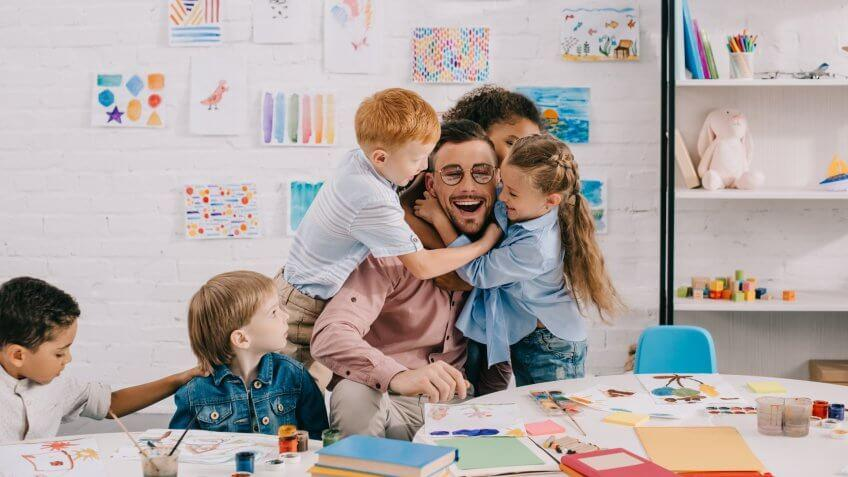interracial kids hugging happy teacher at table in classroom.