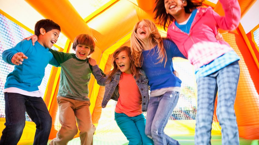 Multi-ethnic group of excited children (ages 7 to 10 years) jumping in inflatable bouncy castle.