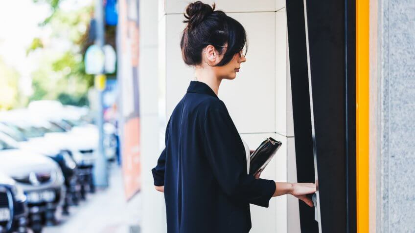 Businesswoman using ATM in city.