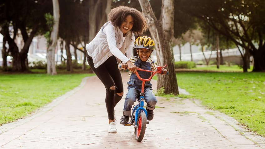 Cute boy learning to ride a bicycle with his mother.