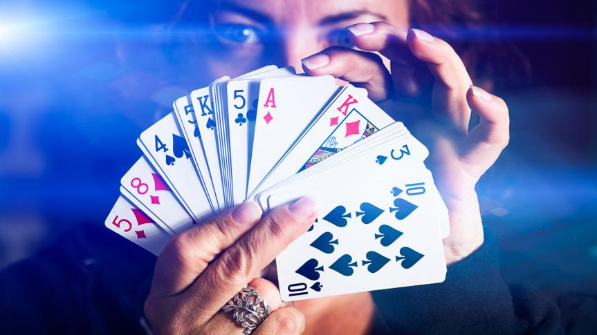 Woman holds up her cards while gambling in a casino.