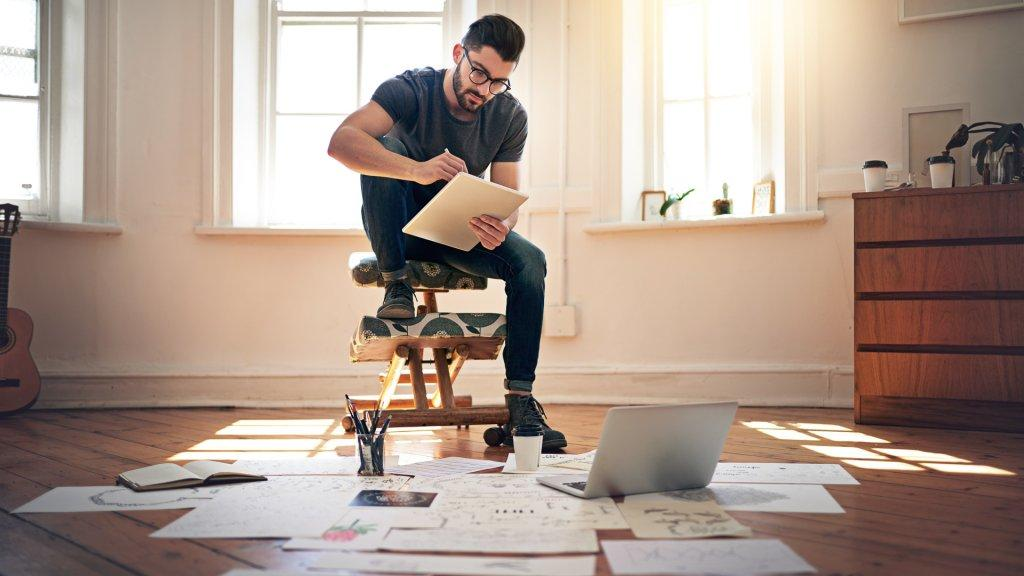 Shot of a designer working on his tablet with designs spread out on the floor in front of him.