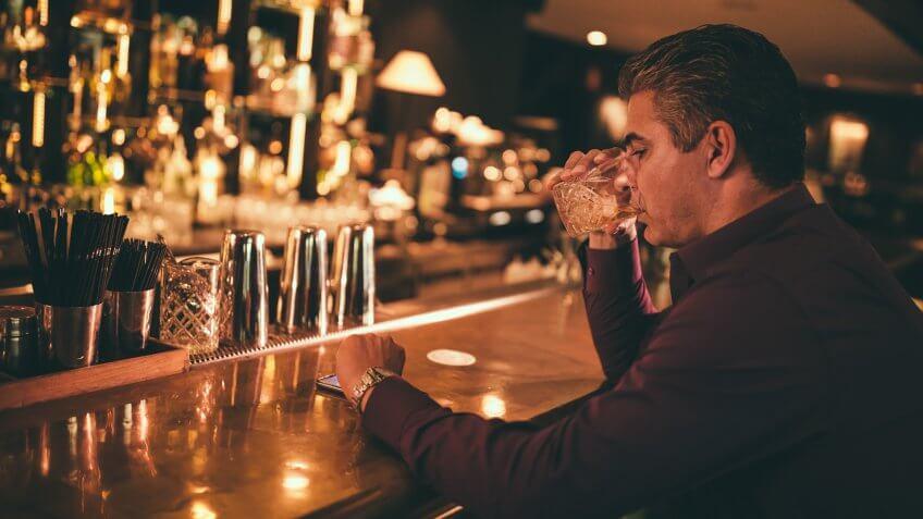 Elegant senior man sitting on bar counter drinking whiskey and looking at watch.