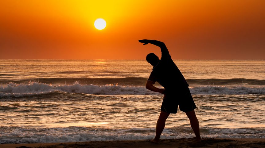 Silhouette of young man doing fitness exercise on the beach at sunrise or sunset.