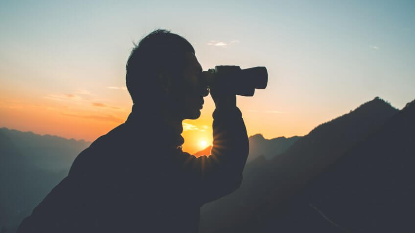 Man looks through binoculars in mountain.