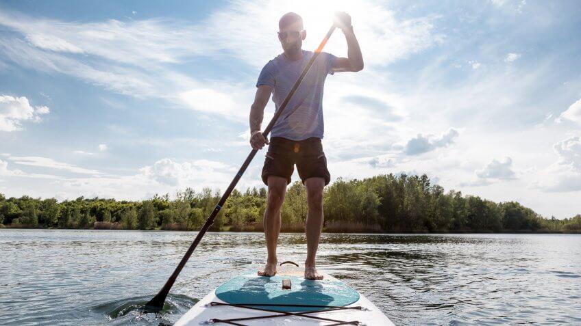 Stand up paddling on a lake.
