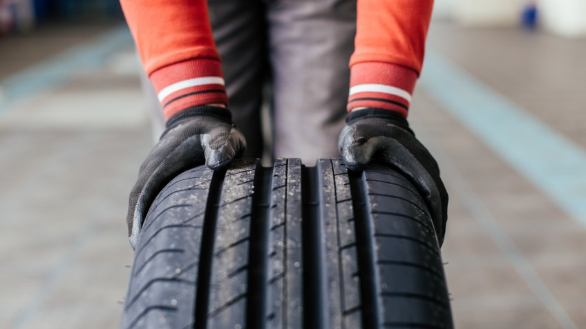 Closeup of mechanic hands holding a black tire in the workshop.