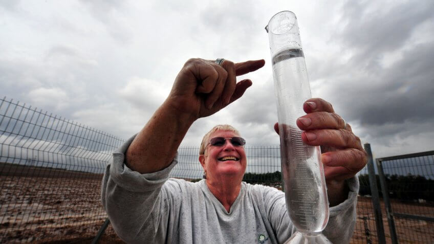Negba, Israel - October 30, 2009: Smiling and happy Meteorologist measures water level in a rain gauges.