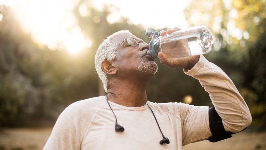 A senior African American Man enjoying refreshing water after a workout.