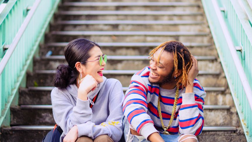 A heterosexual couple sitting outside on a sunny day, looking cheerful.