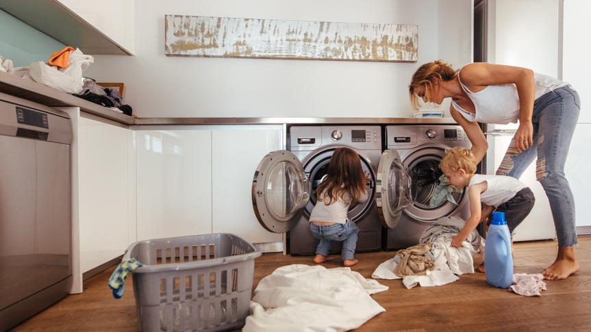 Woman with kids load clothes in washing machine.