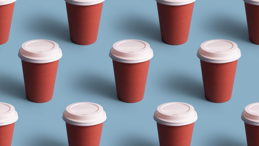 Disposable coffee cups organized in a row over blue background.