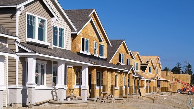 Perspective photo of a row of similar style houses during various phases of construction.