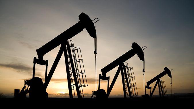 oil industry of three pumpjacks on a prairie at sunrise.