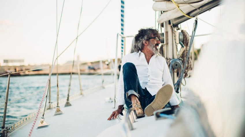 Older man resting on a yacht.