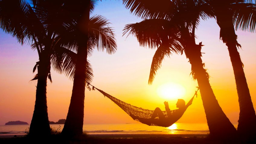 woman relaxing in hammock on beautiful sunset beach, holiday concept.