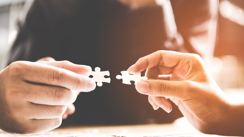 Businessman team work holding pieces two jigsaw connecting couple puzzle piece for matching to goals target, success and start up new project in office.