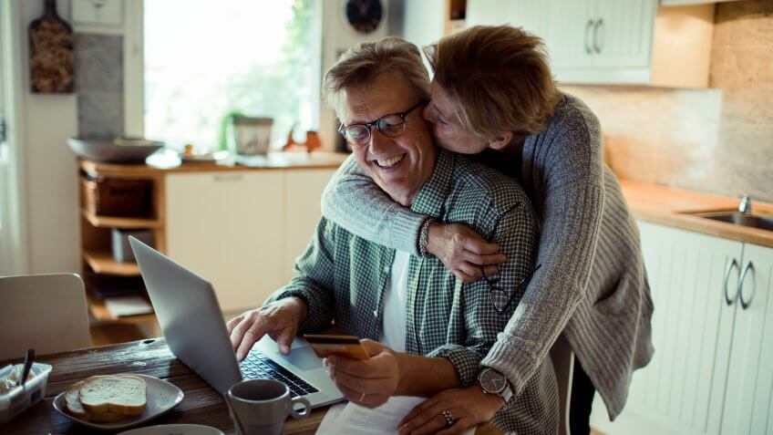Close up of a mature couple doing online shopping in the morning.