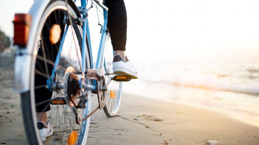 Youn man with classic bike at beach.