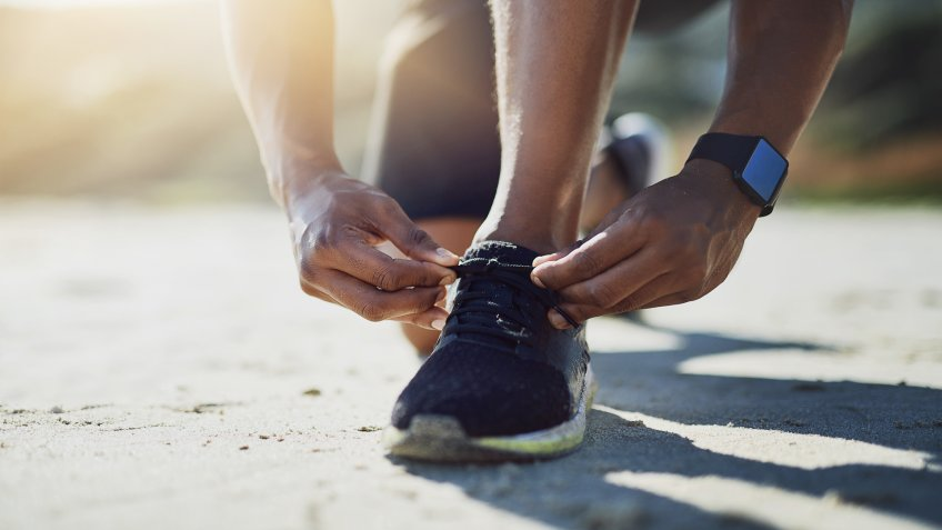 Closeup shot of an unrecognizable man tying his shoelaces while exercising outdoors.