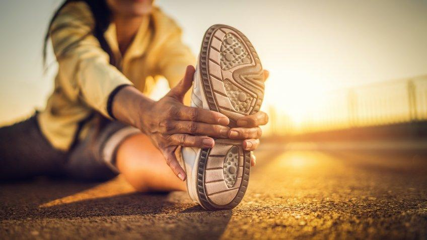 Close-up of athlete's sports shoe during stretching exercises on a road at sunset.