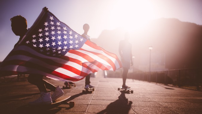 Teenage African American skater flying an American flag past the camera.