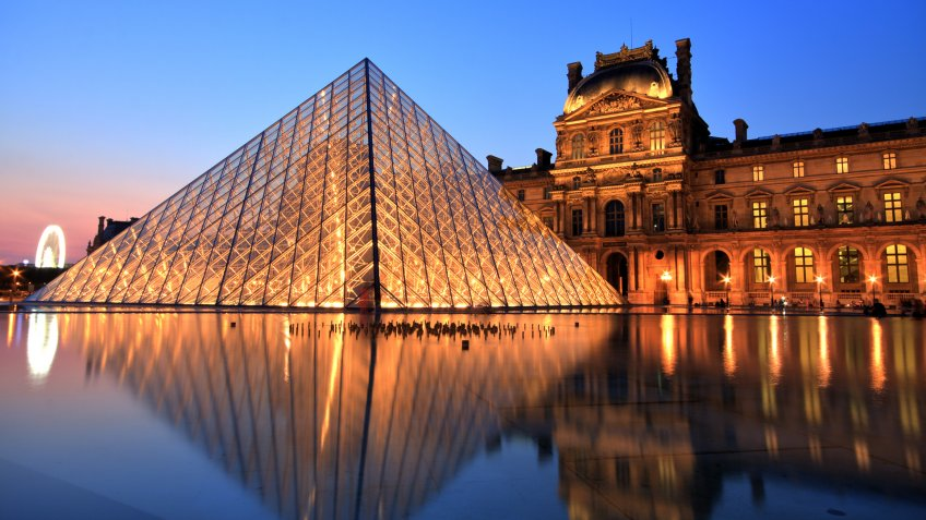 Paris, France - July 6, 2013: Illuminated Louvre museum during sunset in Paris.