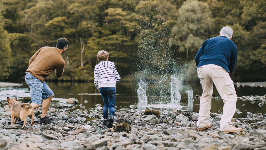 Little boy is skimming pebbles on a lake with his father and grandfather.