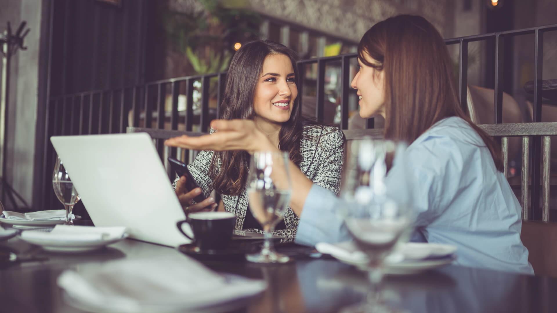 Businesswomen in cafe, using laptop.
